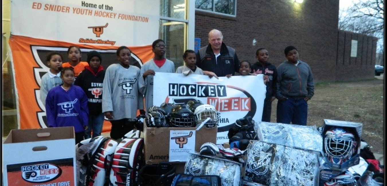 Kids standing with donated equipment and Ed Snider